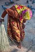 Indian woman sweeping Pushkar lake ghats (India)