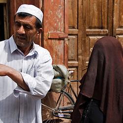 Man giving directions to a veiled woman. Kashgar, Xinjiang, China.
