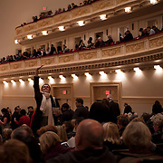 December 12, 2012 - New York, NY : A concertgoer waves toward the balcony as people take their seats ahead of Tuesday evening's performance by the Westminster Symphonic Choir and the Simón Bolívar Symphony Orchestra -- lead by Conductor Gustavo Dudamel -- at Carnegie Hall's Stern Auditorium / Perelman Stage.  CREDIT: Karsten Moran for The New York Times
