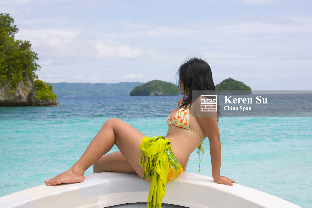 Tourist sitting on boat bow watching landscape, Rock Islands, Palau