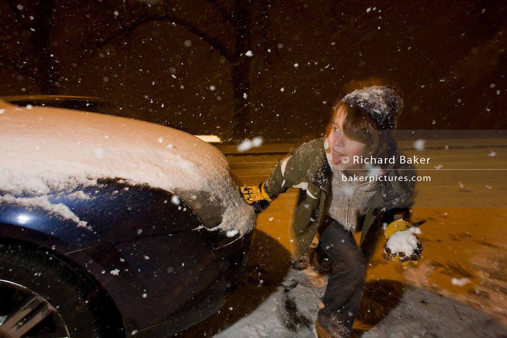 A boy plays snowballs at night during heavy snow showers in central London - a rare event for an inner-city. Snowflakes are falling in large amounts settling on this street in Herne Hill, South London. The lad is in his element by going outdoors at night as the showers are falling everywhere about him. He hides behind a parked car at the kerbside, crouching low to avoid detection by his elder sister. Relishing the hide and seek game they're playing and the prospect of landing the snow as a direct hit makes him look mischievous and excited.