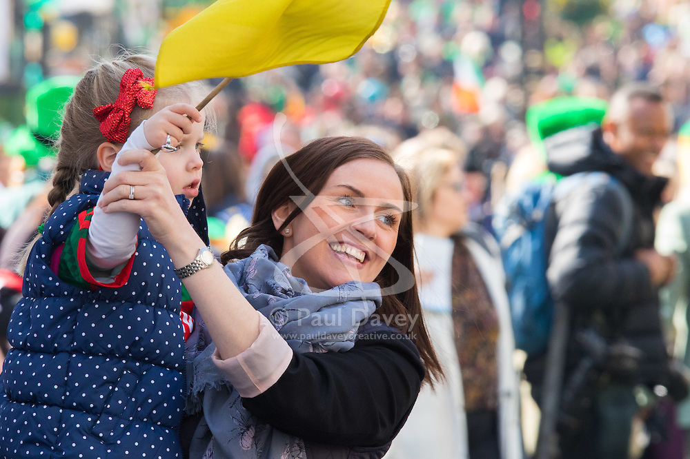 London, March 13th 2016. The annual St Patrick's Day Parade takes place in the Capital with various groups from the Irish community as well as contingents from other ethnicities taking part in a procession from Green Park to Trafalgar Square.  PICTURED: A woman helps a little girl to wave her flag. ©Paul Davey<br /> FOR LICENCING CONTACT: Paul Davey +44 (0) 7966 016 296 paul@pauldaveycreative.co.uk