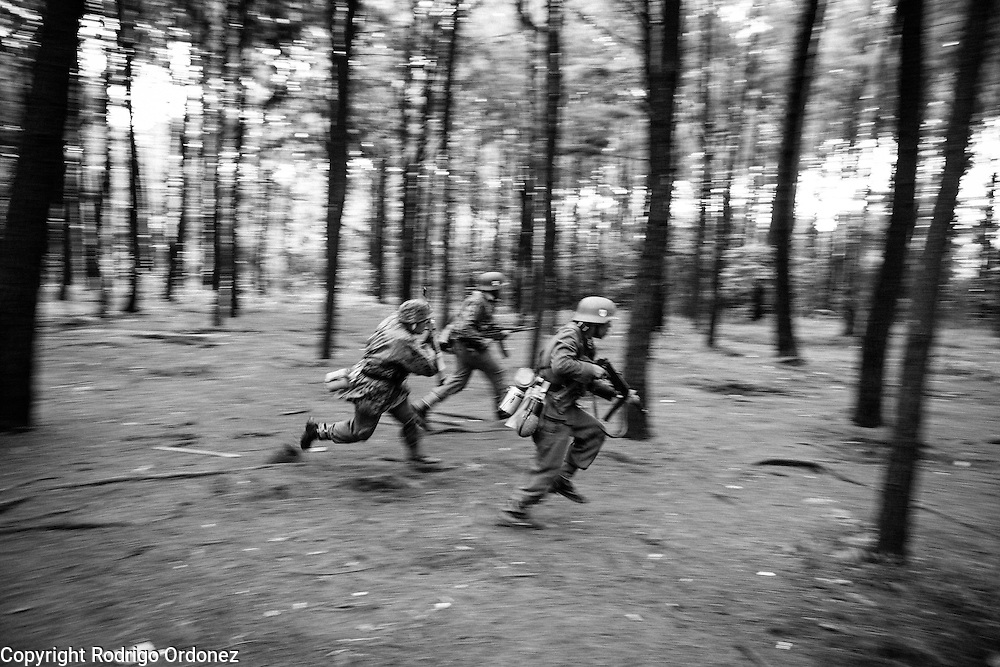 Indonesian men dressed up as German Waffen-SS soldiers run through a pine forest and simulate combat during a gathering of re-enactment enthusiasts in Cibubur, East Jakarta, Indonesia.<br /> Members of the 'Niederlande Kampfgruppe' group meet regularly to re-enact battles wearing Nazi Germany military uniforms and produce their own photos and videos. They claim that they do not do this because they identify ideologically with the Nazis, but because they are interested in World War II and military history. According to them, there is historical evidence that at least one Indonesian person was part of the 'Freiwilligen Legion Niederlande', the Dutch arm of the Waffen-SS, during World War II. Similar re-enactment groups exist in several cities across Indonesia, using the uniforms of Dutch, German and Japanese troops.
