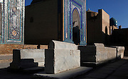 """Low angle view of tombs and in the backround, Mausoleums of the middle group, Shah-i-Zinda Complex, Samarkand, Uzbekistan, pictured on July 19, 2010, in the early morning. The Shah-i-Zinda Complex is a necropolis of mausoleums whose legendary origin dates back to 676 when Kussam-ibn-Abbas arrived to convert the locals to Islam. So successful was he that he was assassinated whilst at prayer. His grave remains the centre of the sacred site which grew over many centuries, especially the 14th and 15th, into an architecturally stunning  example of ceramic art. From left to right """"Nameless 1"""" Mausoleum, 1380s, created by Usto Alim Nesefi, which is decorated  with relief painted majolica. The portal decorations are notable for the symbol of """"octagonal stars""""; on the right of the image is the """"Nameless 2"""" mausoleum, 1390s. Samarkand, a city on the Silk Road, founded as Afrosiab in the 7th century BC, is a meeting point for the world's cultures. Its most important development was in the Timurid period, 14th to 15th centuries. Picture by Manuel Cohen."""