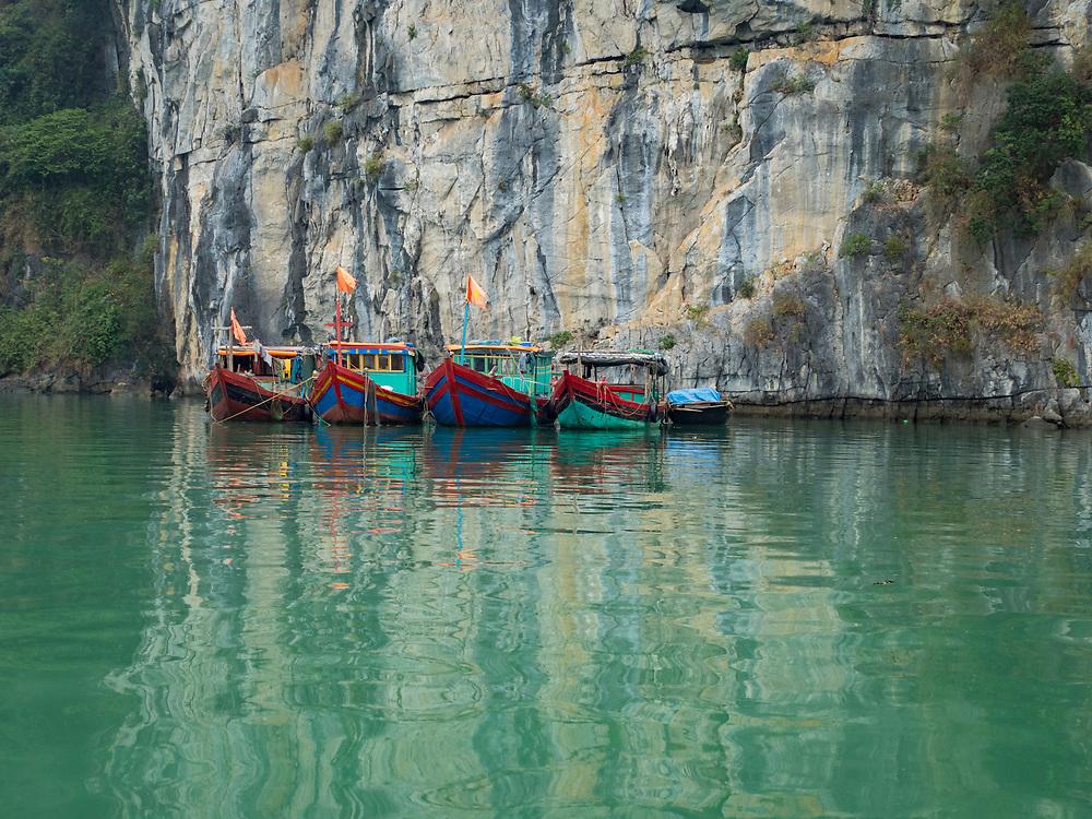 Asia, Viet Nam, Bái Tu Long Bay, Bái Tu Long National Park. Boat at anchor below a cliff.