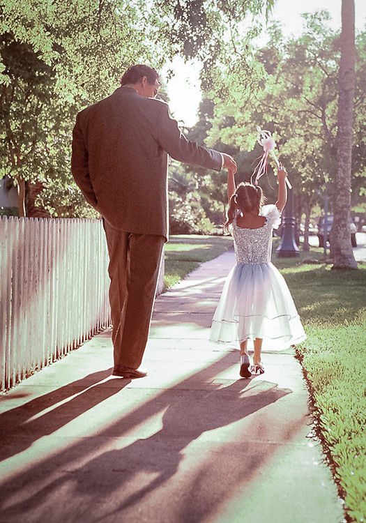 Father walking with daughter dressed as princess