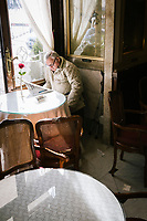 """NAPLES, ITALY - 24 NOVEMBER 2018: A customer reads the newspaper in the Tea Room of  Bar Gambrinus, in Naples, Italy, on November 24th 2018.<br /> <br /> My Brilliant Friend (Italian: L'amica geniale) is an Italian-American drama television miniseries based on the novel of the same name by Elena Ferrante. The series follows the lives of two perceptive and intelligent girls, Elena (sometimes called """"Lenù"""") Greco and Raffaella (""""Lila"""") Cerullo, from childhood to adulthood and old age, as they try to create lives for themselves amidst the violent and stultifying culture of their home – a poor neighborhood on the outskirts of Naples, Italy. My Brilliant Friend is a co-production between American premium cable network HBO and Italian networks RAI and TIMvision"""