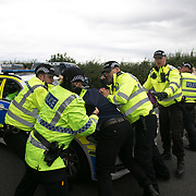 Anti-fracking  activists and protesters outside the gates of Quadrilla's fracking site June 31st, New Preston Road, Lancashire, United Kingdom.  As a truck with equipment arrives police move in to clear the road. The struggle against fracking in Lancashire has been going on for years. The fracking company Quadrilla is finally ready to bring in a drill tower to start drilling and anti-frackinhg activists are waiting in front of the gates to block the equipment getting in. Fracking is a destructive and potential dangerous and highly contentious method of extracting gas and this site will be the first of many in the United Kingdom reaching miles out under ground.
