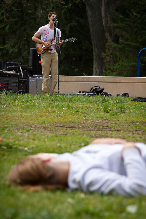 Ethan Kenvarg '12, left, belts out vocals as a Grinnellian concertgoer relaxes on the JRC courtyard grass. BEN BREWER/Grinnell College
