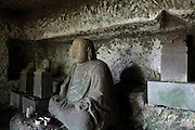 old weathered Buddha monument and decapitated small Buddhist sculptures in a Yagura Japan