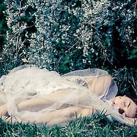 Young woman wearing a lace dress lying alone on grass