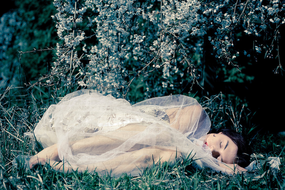 Young woman wearing a lace dress lying alone on grass