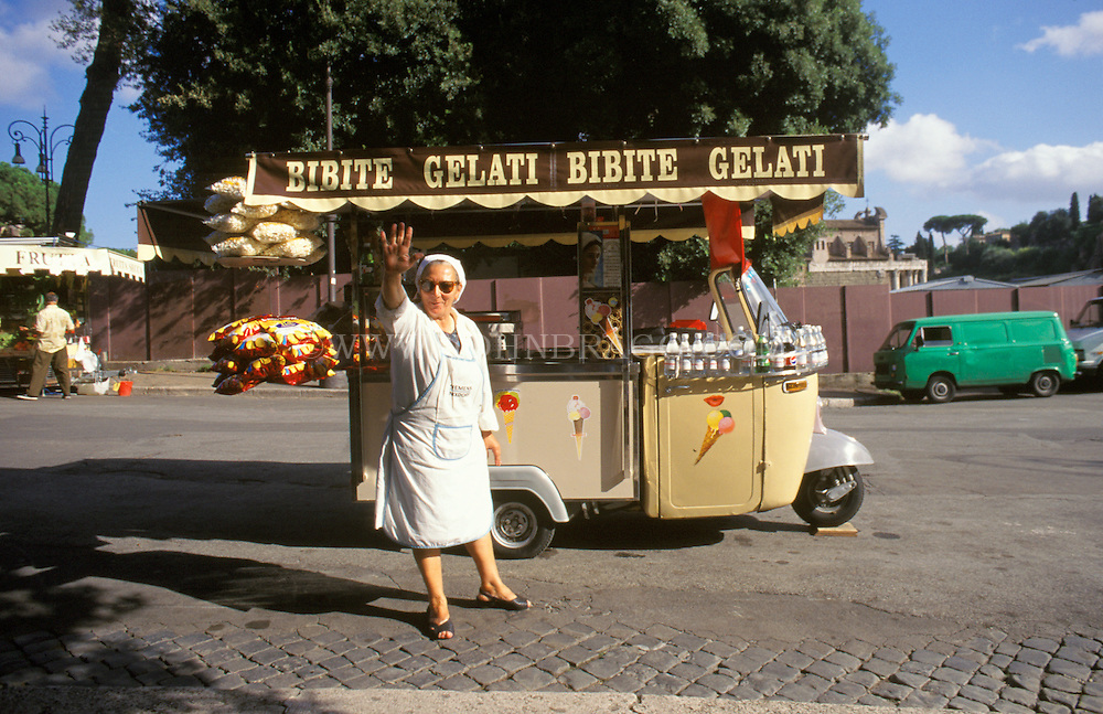 Woman waving with a gelato truck in Rome, Italy.