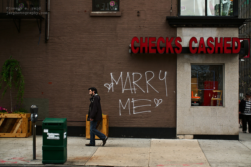 "Man walking past words ""Marry Me"" spraypainted on side of building, Brooklyn, NY, US"