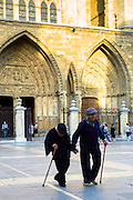 Elderly couple with walking sticks leave after Catholic Mass at Santa María de León Cathedral in Leon, Castilla y Leon, Spain