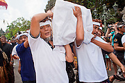 Apr. 25 -- UBUD, BALI, INDONESIA:  Pall bearers carry the coffin during the funeral for Cokorde Gede Raka, a member of Ubud's royal family Sunday, Apr. 25. Balinese are Hindus and cremate their dead. Balinese funerals are elaborate - and expensive - affairs. A funeral for one person costs a minimum of 45 million rupiah (about $5,000 US). The body is placed into the bull's body at the cremation and cremated in the bull. The funeral pyre is burnt adjacent to the bull. That is what a family may earn in two to three years. The result is that only the rich can afford formal cremations. The body (in the casket) is placed in the top of the funeral pyre and the procession takes the body to the cremation site. The funeral pyre, and the body, are spun at intersections to confuse the spirits so the soul doesn't try to return to its home and to confuse evil spirits.    PHOTO BY JACK KURTZ