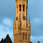 The iconic Belfry of Brug catches the first rays of sunshine after sunrise. The Belfry (or Belfort) is a medieval bell tower standing above the Markt in the historic center of Bruges. The first stage was built in 1240, with further stages on top built in the late 15th century.