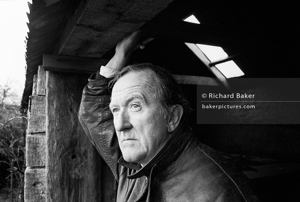 A portrait of English poet, lecturer, actor and broadcaster Patrick J. Kavanagh. We see him reaching to hold a beam outside his home in the Cotswolds, Gloucestershire, England. P J Kavanagh (born 6 January 1931) is the author of eight books of poems, an essayist and travel-writer, a novelist, and editor of the poems of Ivor Gurney; he has received the Cholmondely Award for Poetry, the Guardian Fiction Prize, and the Richard Hillary Prize for his memoir The Perfect Stranger. In addition to this literary career, he has been an actor, lecturer, journalist and broadcaster, all after serving in the Army during the Korean War, where he was wounded in action.