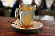 A glass of hot water with lemon and honey out of focus people in the background