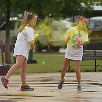Avery Anthony, 13, left,  and Mamie McGraw, 13, has fun throwing the colored starch onto each other before the Color Vibe 5K Run gets underway on Saturday.