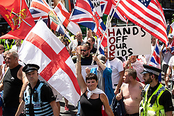 """© Licensed to London News Pictures . 07/07/2018 . Leeds , UK . An anti-Islam march by supporters of jailed EDL founder Tommy Robinson , including those from the """" Yorkshire Patriots """" and """" First for Britain """" , in Leeds City Centre , opposed by anti-fascists . Robinson ( real name Stephen Yaxley-Lennon ) was convicted of Contempt of Court in May 2018 after committing a second offence , whilst serving a suspended sentence for the same crime . Photo credit : Joel Goodman/LNP"""
