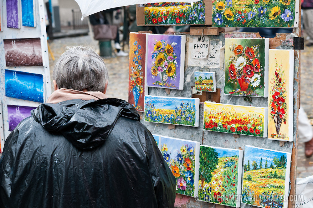 A painter has his paintings for sale at Montremartre market next to Sacre Coeur Cathedral, Paris.