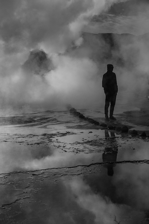 A man stands in front of a big geyser at sunrise, Et Tatio geyser field, Chile.