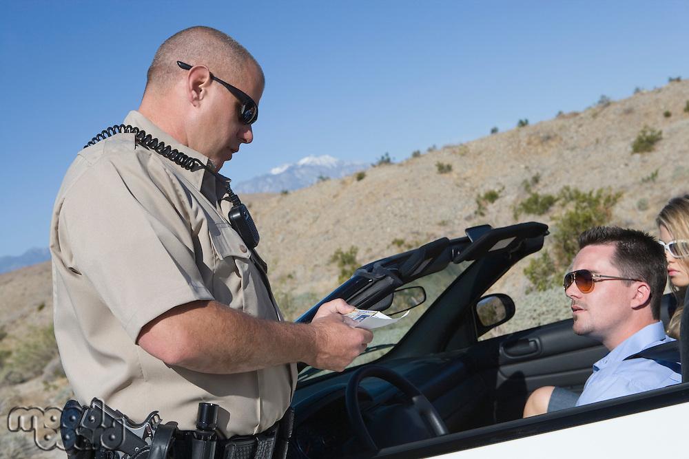 Police officer checking on driver in desert