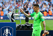 Ederson Moraes (31) of Manchester City places the FA Cup on the podium during the celebrations at full time during the The FA Cup Final match between Manchester City and Watford at Wembley Stadium, London, England on 18 May 2019.