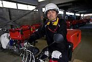 Yoichi Kawashima, a postman at the Ishinomaki branch of Japan Post Service Co., Ltd. drives his motorbike through the company's garages in Ishinomaki, Miyagi Prefecture, Japan on Tuesday 24 May 2011..Photographer: Robert Gilhooly.
