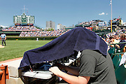 CHICAGO, IL - MAY 29: A photographer braves foul balls while editing in the photo well under a bath towel during the game between the San Diego Padres and Chicago Cubs at Wrigley Field on May 29, 2012 in Chicago, Illinois. The Cubs managed a 5-3 win. (Photo by Joe Robbins)