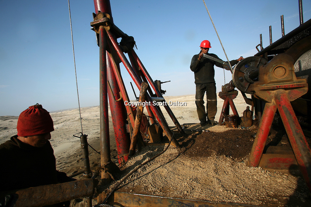 Non-union contract laborers work to pull oil from a well at a field owned and operated by SAPET, a Chinese oil company, in Talara, on Peru's northern coast, on November 8. 2007. (Photo/Scott Dalton)