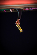 A man dangles beads from his balcony above Bourbon Street during Mardi Gras in New Orleans, Louisiana