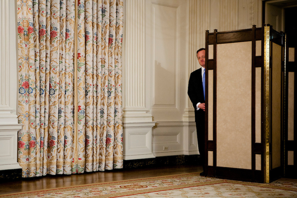 White House Press Secretary Robert Gibbs listens as President Barack Obama delivers a statement on the situation in Egypt at the White House in Washington, D.C., U.S., on Friday, January 28, 2011.
