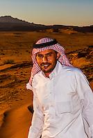 Bedouin man standing on a sand dune,  Arabian Desert, Wadi Rum, Jordan.