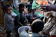 "Group of boys cut pieces of meat to serve during an early marriage celebration of two young girls. Child marriages may have many purposes: In the lower classes, if they were fortunate, families could use child marriages as a means to gain financial ties with wealthier people, ensuring their successions. During the last years, luckily, people are beginning to understand that this traditional practice is doing irreparable harm to their daughters. North West of Ethiopia, on saturday, Febrary 14 2009.....In a tangled mingling of tradition and culture, in the normal place of living, in a laid-back attitude. The background of Ethiopia's ""child brides"", a country which has the distinction of having highest percentage in the practice of early marriages despite having a law that establishes 18 years as minimum age to get married. Celebrations that last days, their minds clouded by girls cups of tella and the unknown for the future. White bridal veil frame their faces expressive of small defenseless creatures, who at the age ranging from three to twelve years shall be given to young brides men adults already...To protect the identities of the recorded subjects names and specific places are fictional."