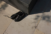 A brand new pair of unlaced, unworn shoes left alongside anonymous boot prints on a City of London pavement.