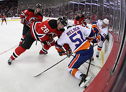Mar 8; Newark, NJ, USA; New Jersey Devils defenseman Anton Volchenkov (28) battles for the loose puck against New York Islanders center Frans Nielsen (51) and New York Islanders center Josh Bailey (12) during the first period at the Prudential Center.