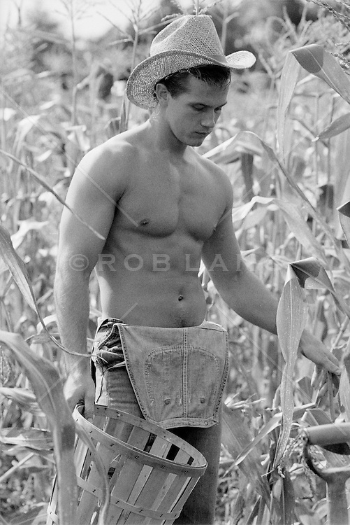 All American farmer without a shirt in a corn field