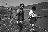 Men fishing to supplement their incomes at the Papan reservoir, near the city of Osh, once one of the great cities of the Silk Road and of Central Asia, and the second biggest city in the country, situated in the unstable Ferghana valley which is now becoming a hotbed if Islamic Fundamentalism, Osh,  Kyrgyzstan.
