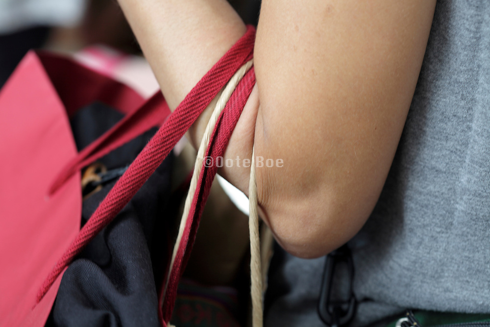 close up of adult woman holding bags on her arm