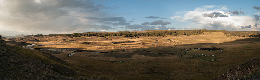 A panorama of the Hayden Valley lit up by the afternoon sun in autumn in Yellowstone National Park, USA.