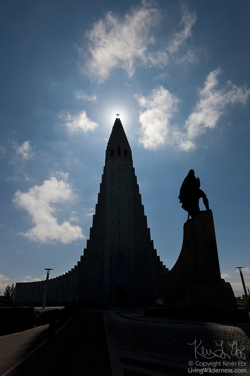 The midday sun shines behind the cross atop Hallgrímskirkja, a Lutheran church and prominent landmark in Reykjavík, Iceland. Icelandic architect Guðjón Samúelsson designed the church to resemble the basalt columns found around Iceland. Construction of Hallgrímskirkja took 38 years, reaching completion in 1986. Also visible in this image is a Leif Eriksson Memorial, which the United States gave to Iceland in 1930 to celebrate the 1000th anniversary of Iceland's parliament at Þingvellir.