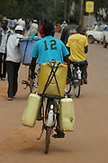 Modes of transport on Africa's dusty roads. A man uses his bike to transport containers of water. Uganda, Africa.