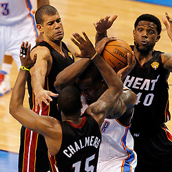 Jun 14, 2012; Oklahoma City, OK, USA;  Oklahoma City Thunder center Kendrick Perkins (5) rebounds against Miami Heat point guard Mario Chalmers (15) and power forward Udonis Haslem (40) and small forward Shane Battier (31)  during the third quarter of game two in the 2012 NBA Finals at Chesapeake Energy Arena. Mandatory Credit: Derick E. Hingle-US PRESSWIRE