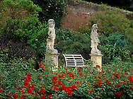A walled garden at  Polesden Lacey with a pair of<br /> garden statues and a bench surrounded by red rosa<br /> June  Surrey  England