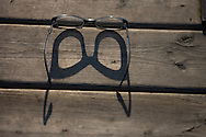 © 2008 Randy Vanderveen, all rights reserved.Grande Prairie, Alberta.A pair of glasses sit in the morning sun on a wooden dock.