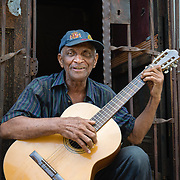 Portrait of man playing guitar on a doorstep in Havana