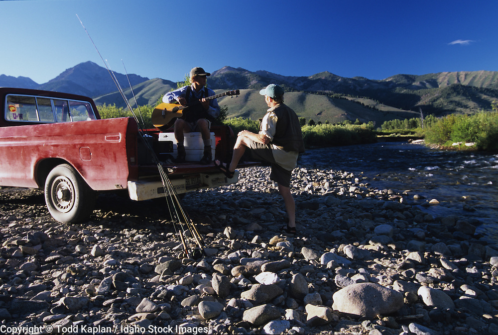 Idaho, near Sun Valley, Big Wood River.  Tow fly fishermen sitting on tail bed of old truck wating for the hatch.