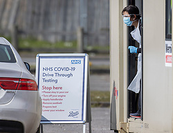 © Licensed to London News Pictures. 28/03/2020. Chessington, UK. A nurse (R) talks to a driver as she prepares to take a swab at a newly opened drive through virus testing centre for NHS staff in the car park of Chessington World of Adventures. Death rates from the spread of coronavirus continue to climb. Both the Prime Minister Boris Johnson and Health Secretary Matt Hancock have tested positive for the virus and are now self isolating. Photo credit: Peter Macdiarmid/LNP